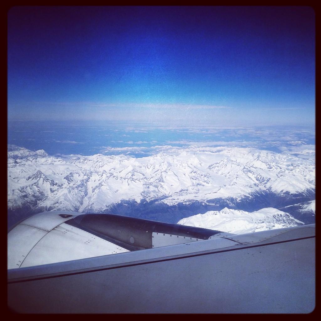 Vue depuis le hublot d'un avion, les Alpes en contrebas.
