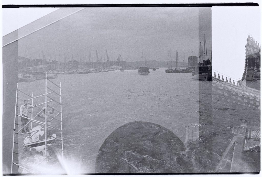Des ouvriers réparent une façade de la Cité interdite sur le fond de la Marina de Trogir