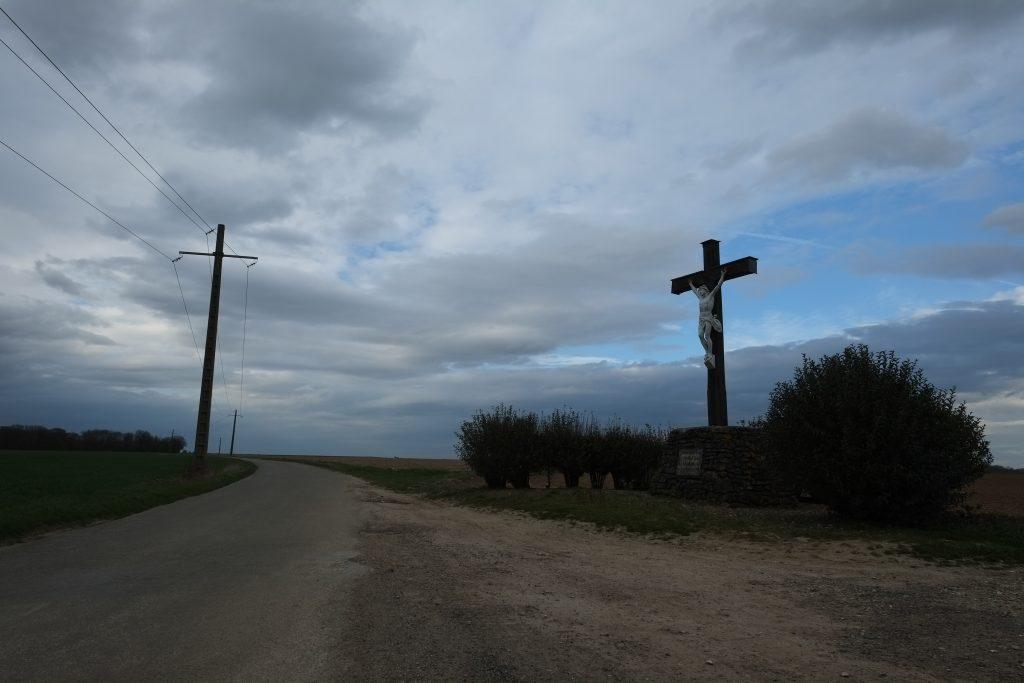 Mimétisme sur le bord d'une route entre un cricifix et un pylône.