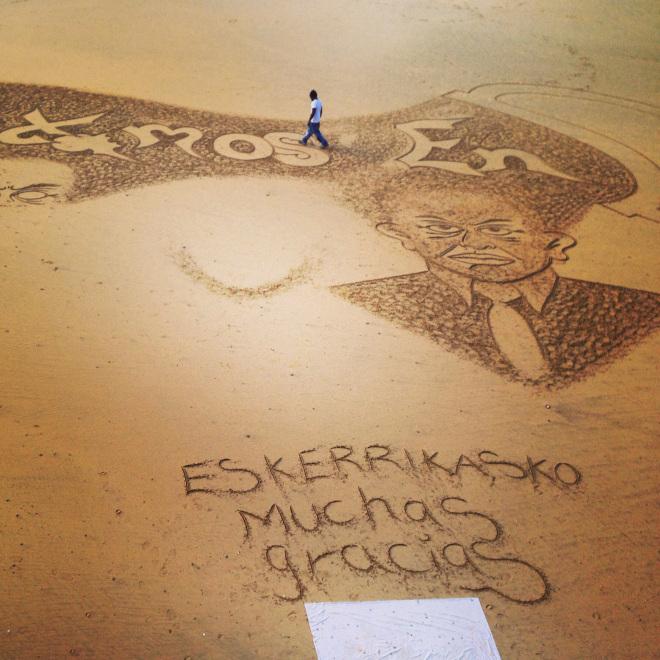 Un artiste dessine sur le sable de la plage de la Concha