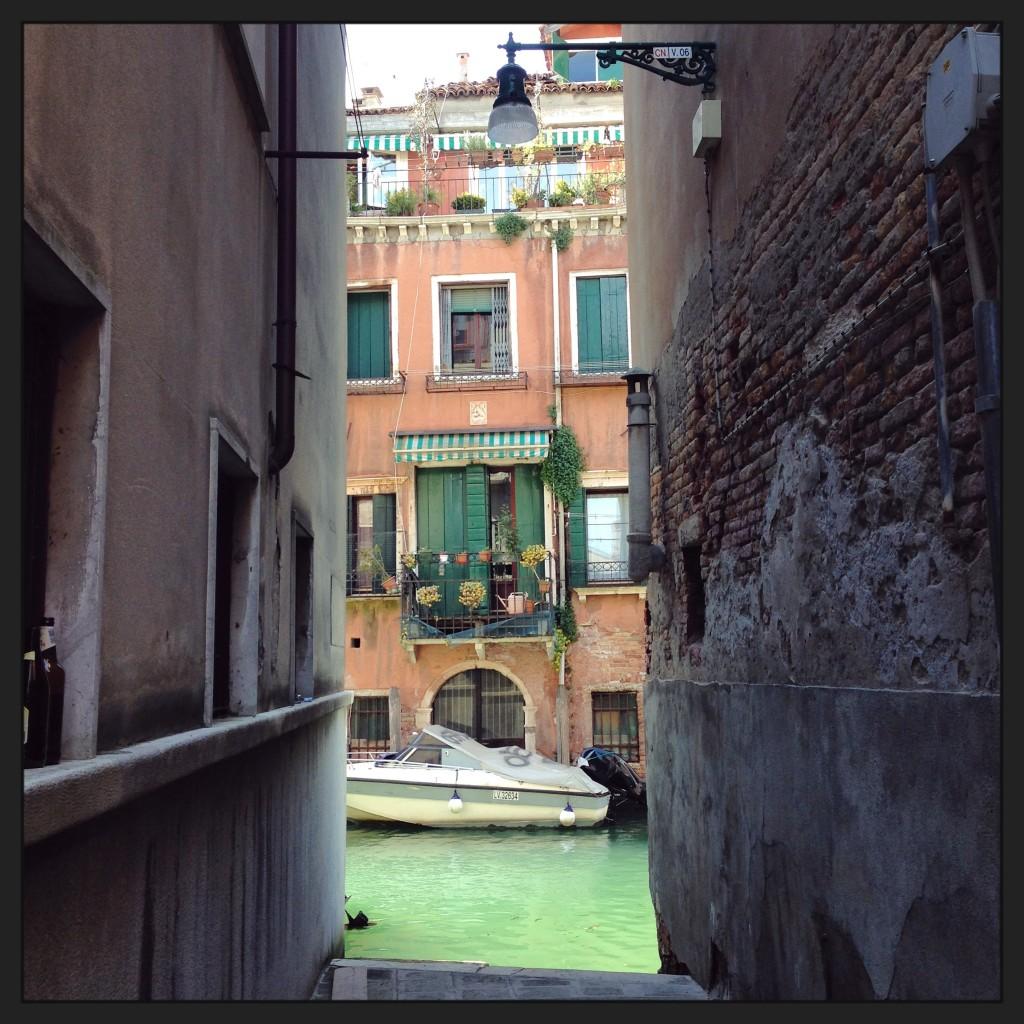 Une ruelle débouche sur un petit canal vert émeraude