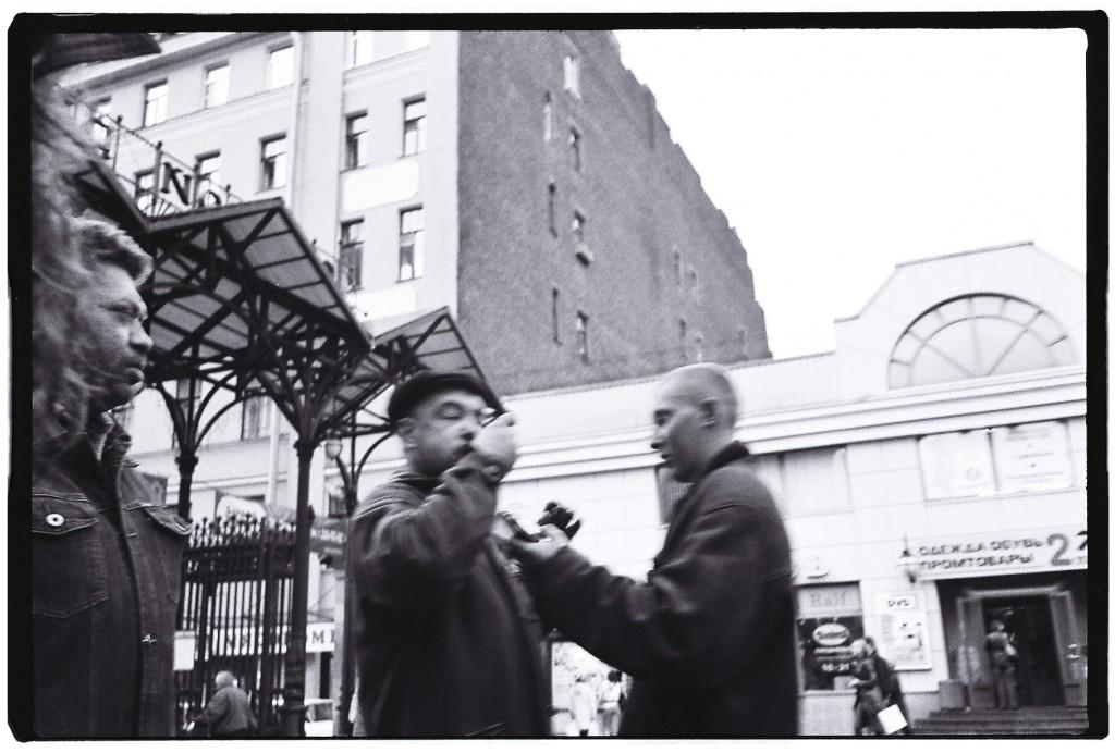 Des hommes traînent à l'entrée d'un petit marché urbain