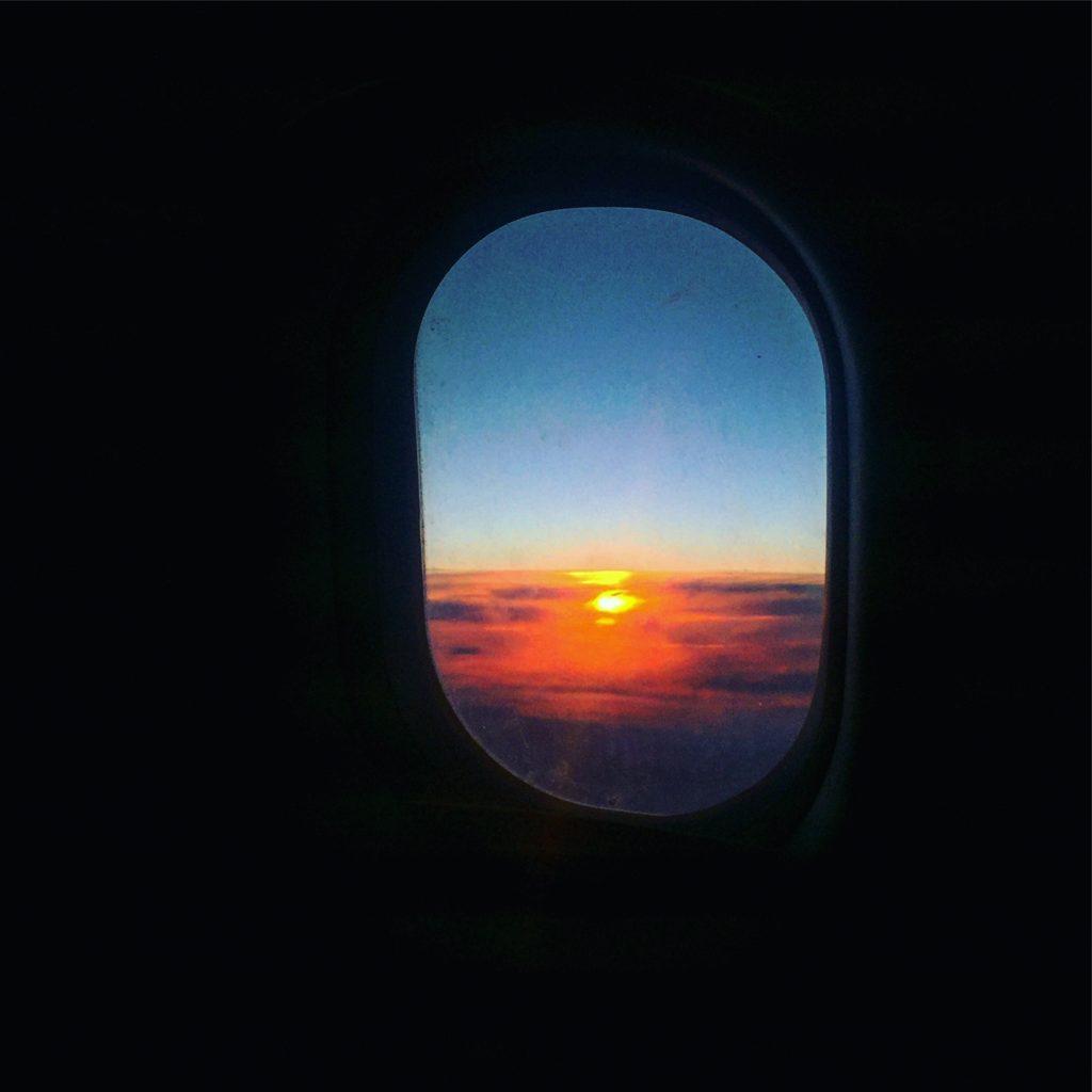 Vue d'un coucher de soleil depuis le hublot d'un avion