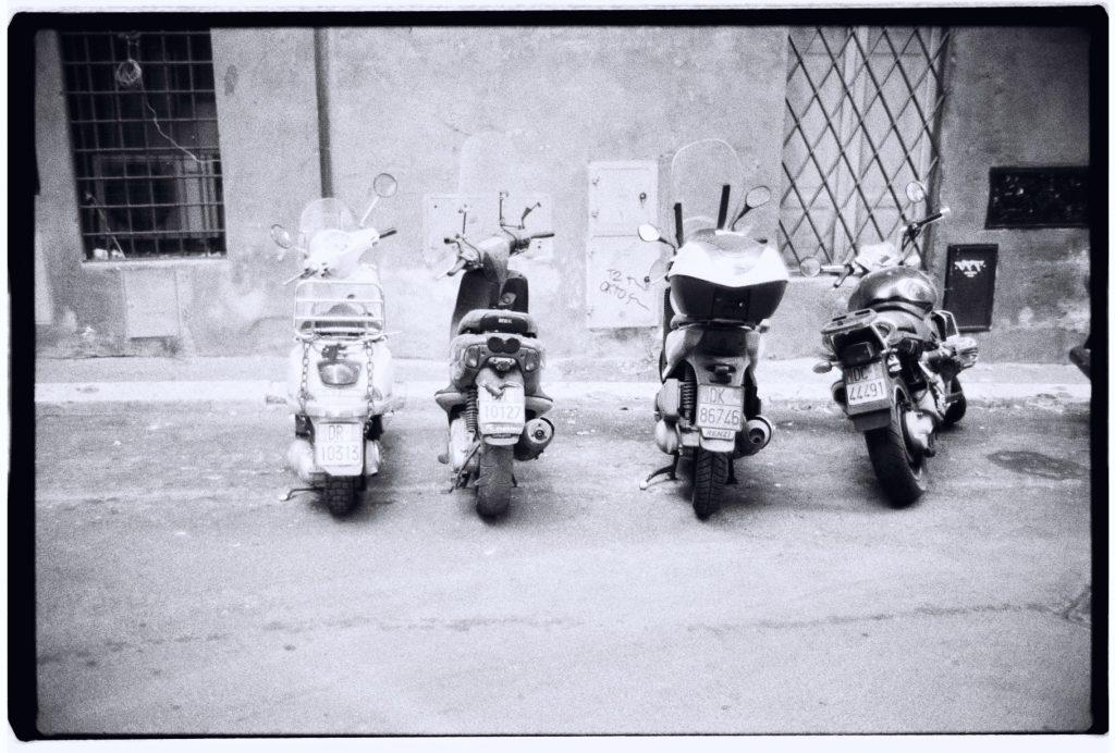 Des scooters stationnés dans une petite rue de Rome