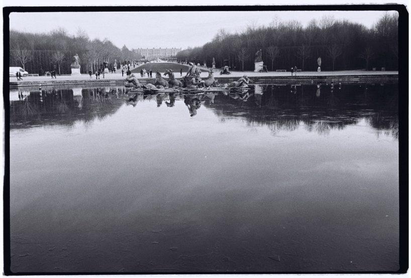 Une fontaine et le château de Versailles dans les lointains