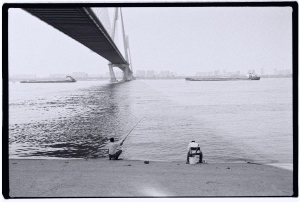 Des pêcheurs à l'ombre d'un pont sur les rives du Yangzi Jiang