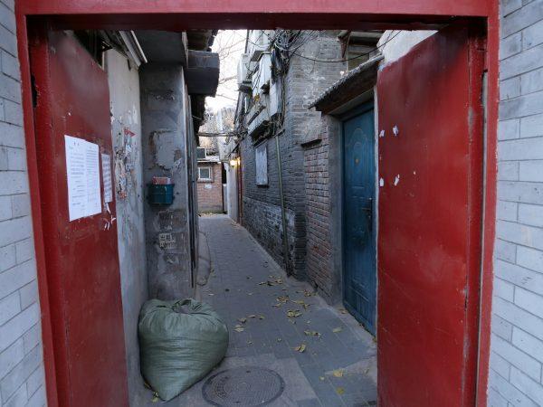 Une porte rouge marquant l'entrée dans un hutong à pékin