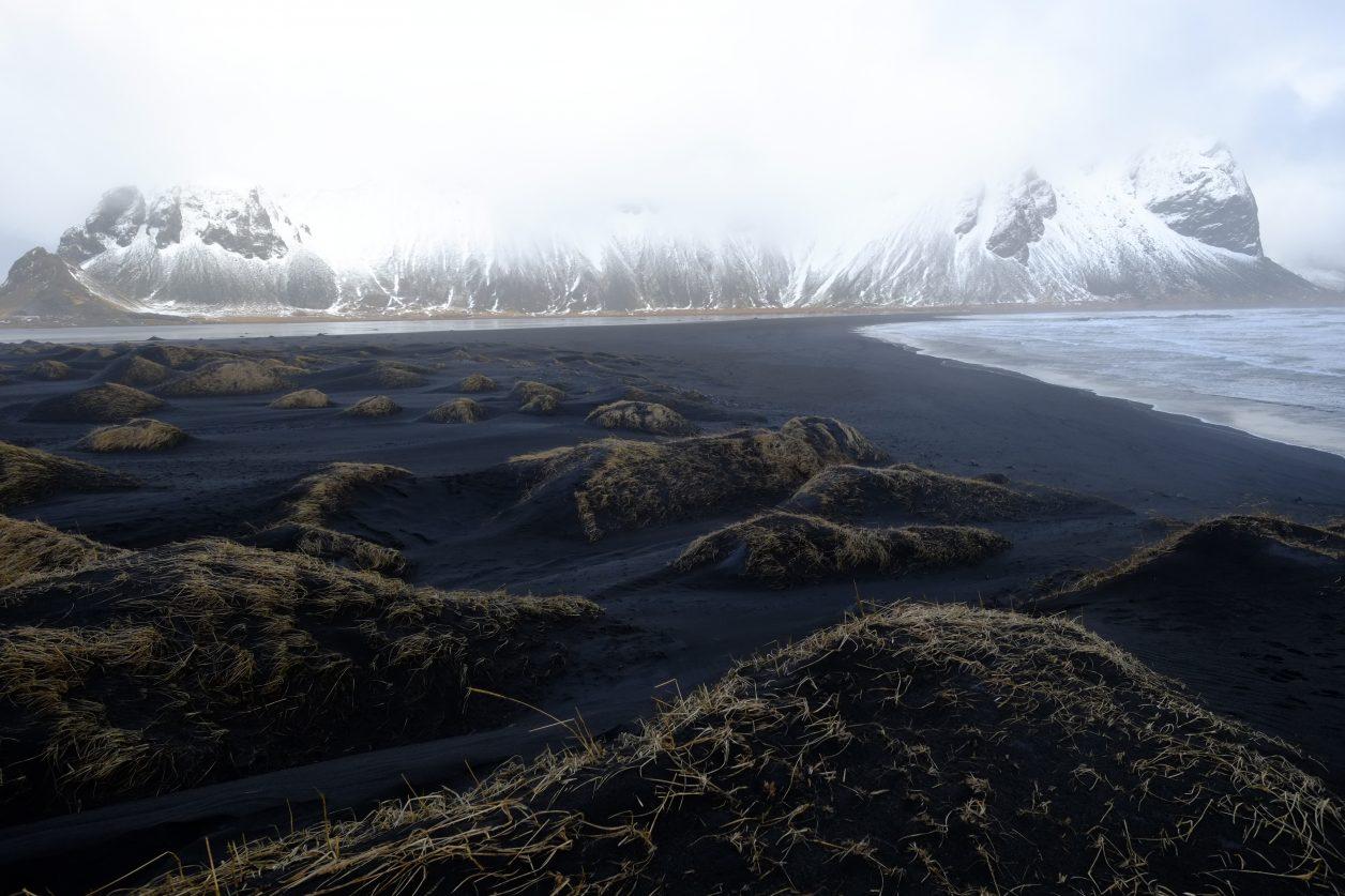 Du brouillard sur les montagnes, un vent fort et une plage de sable noir