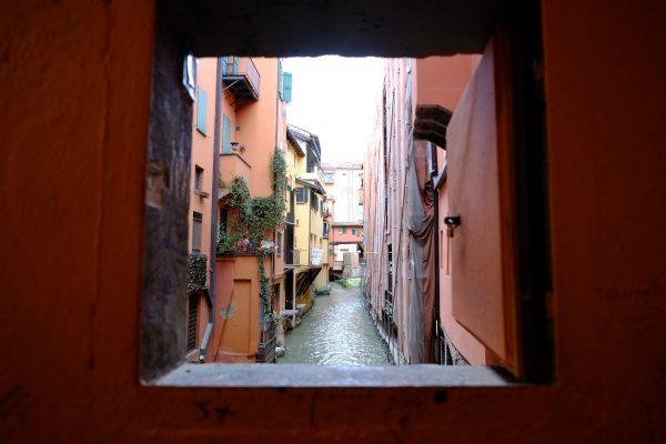 La vue depuis une petite fenêtre sur un canal à Bologne