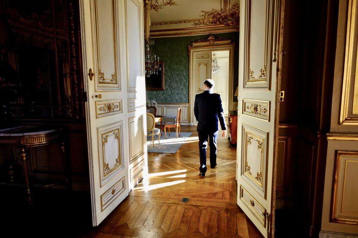 Un huissier marchant dans le long couloir du Département