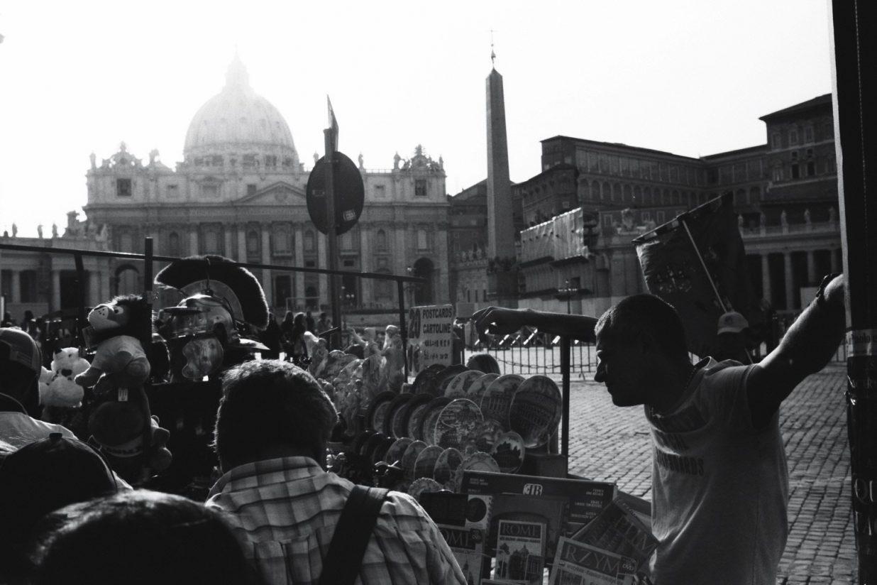Quelques touristes se pressent autour d'un homme avec les bras en croix