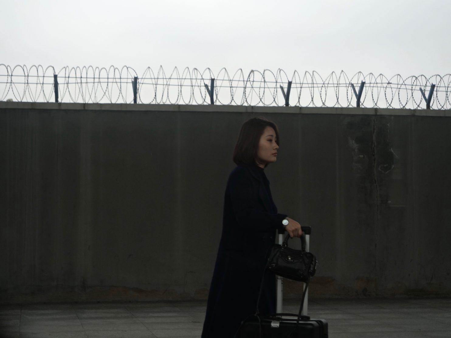 Une femme d'affaire chinoise attendant le train à grande vitesse chinois Hexie