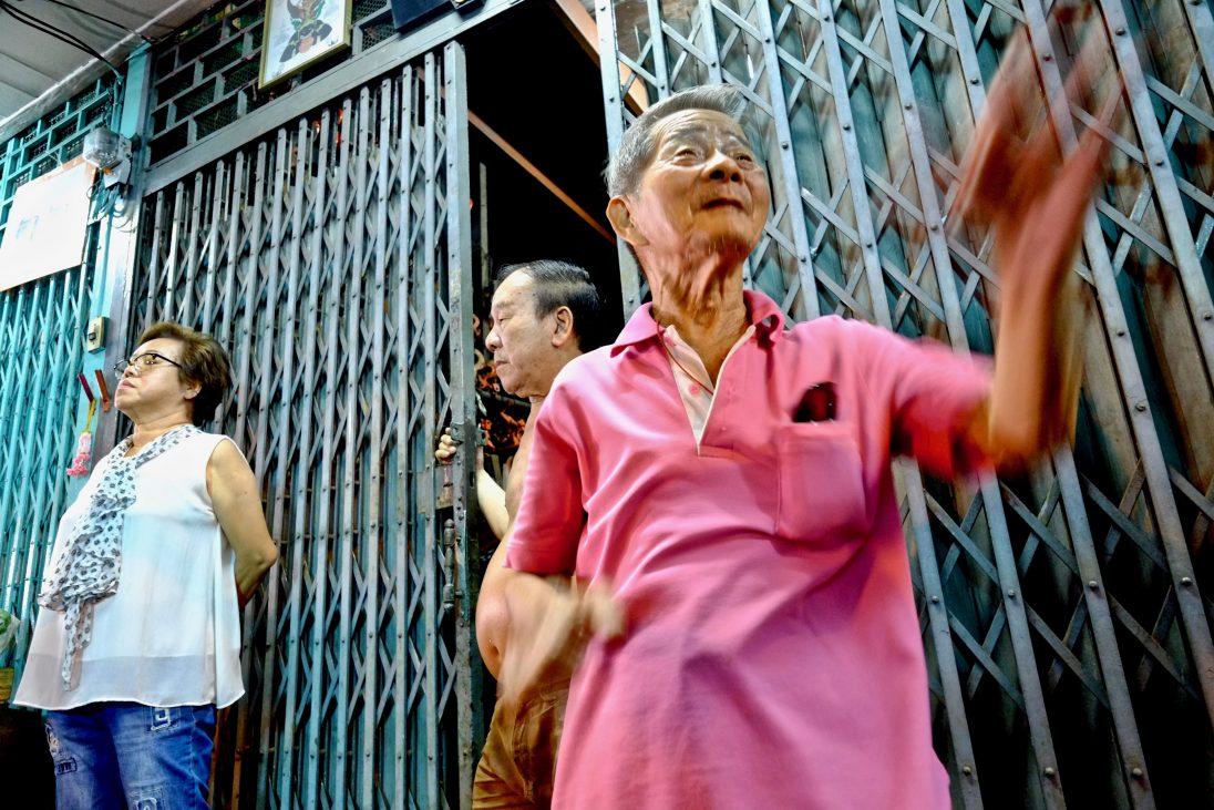 Des commerçants dans le quartier chinois de Bangkok regardant passer le carnaval pendant la fête du dragon