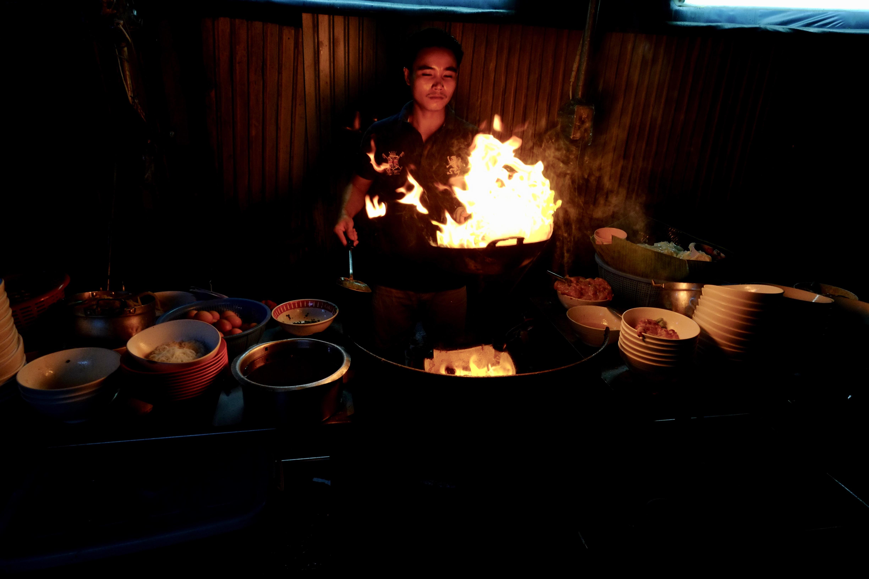 Un cuisinier dans une arrière cour préparant la fameuse street food Thaïlandaise