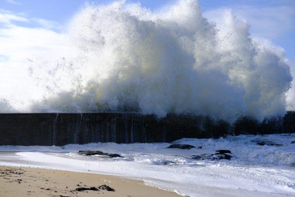 Une jolie vague s'écrasant sur une digue et une tempête sous le soleil