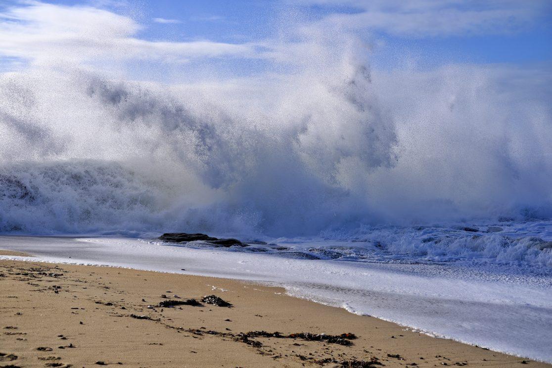 Une vague dont l'écume recouvre totalement la digue de Batz