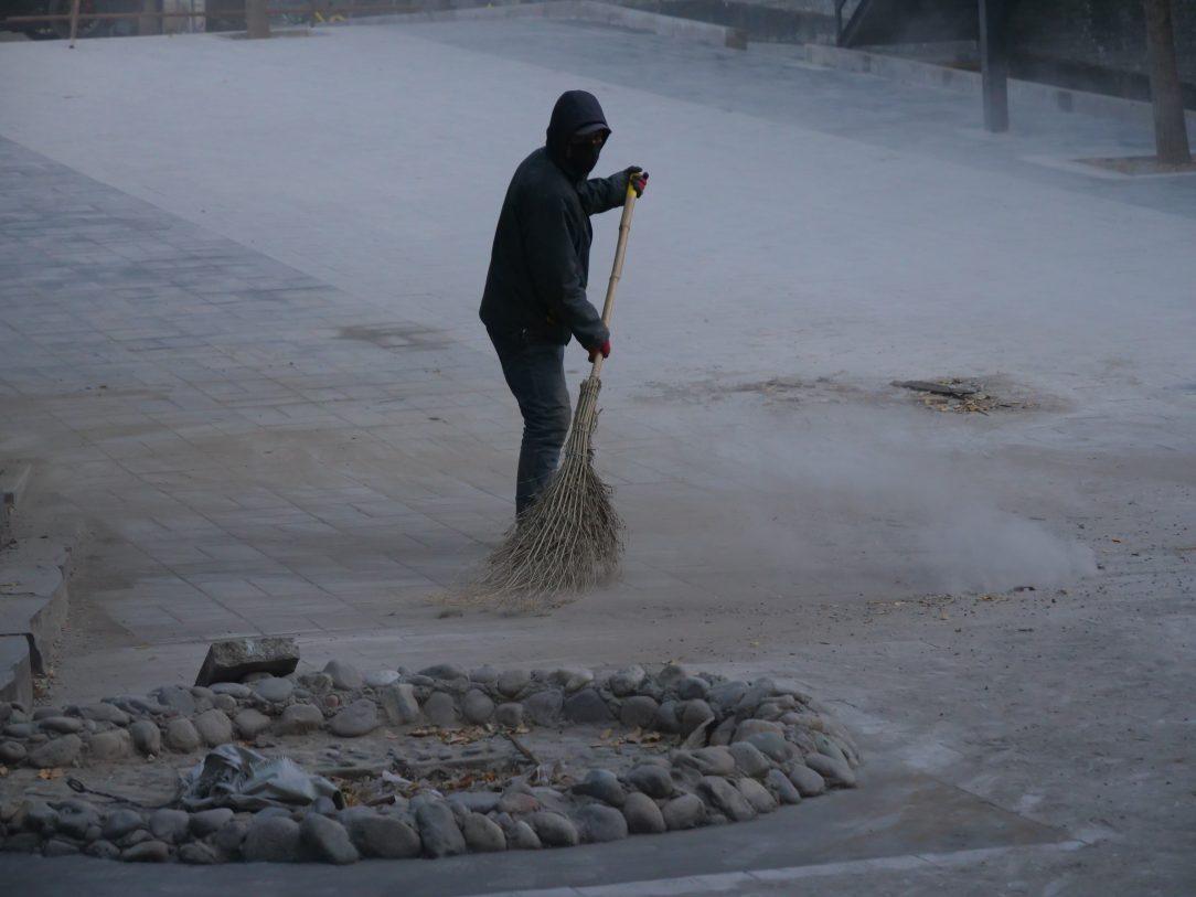Un ouvrier nettoyant la rue après des travaux