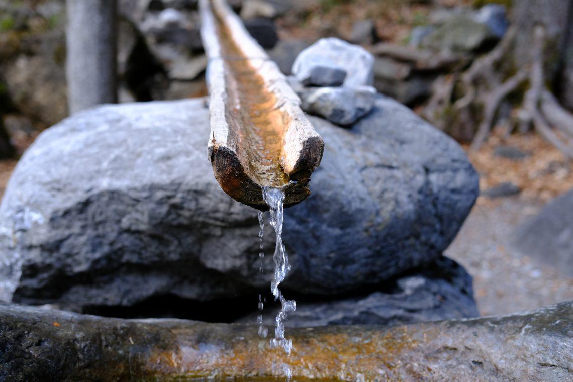 Une fontaine le long d'un petit chemin en Suisse, photographe Yann Vernerie