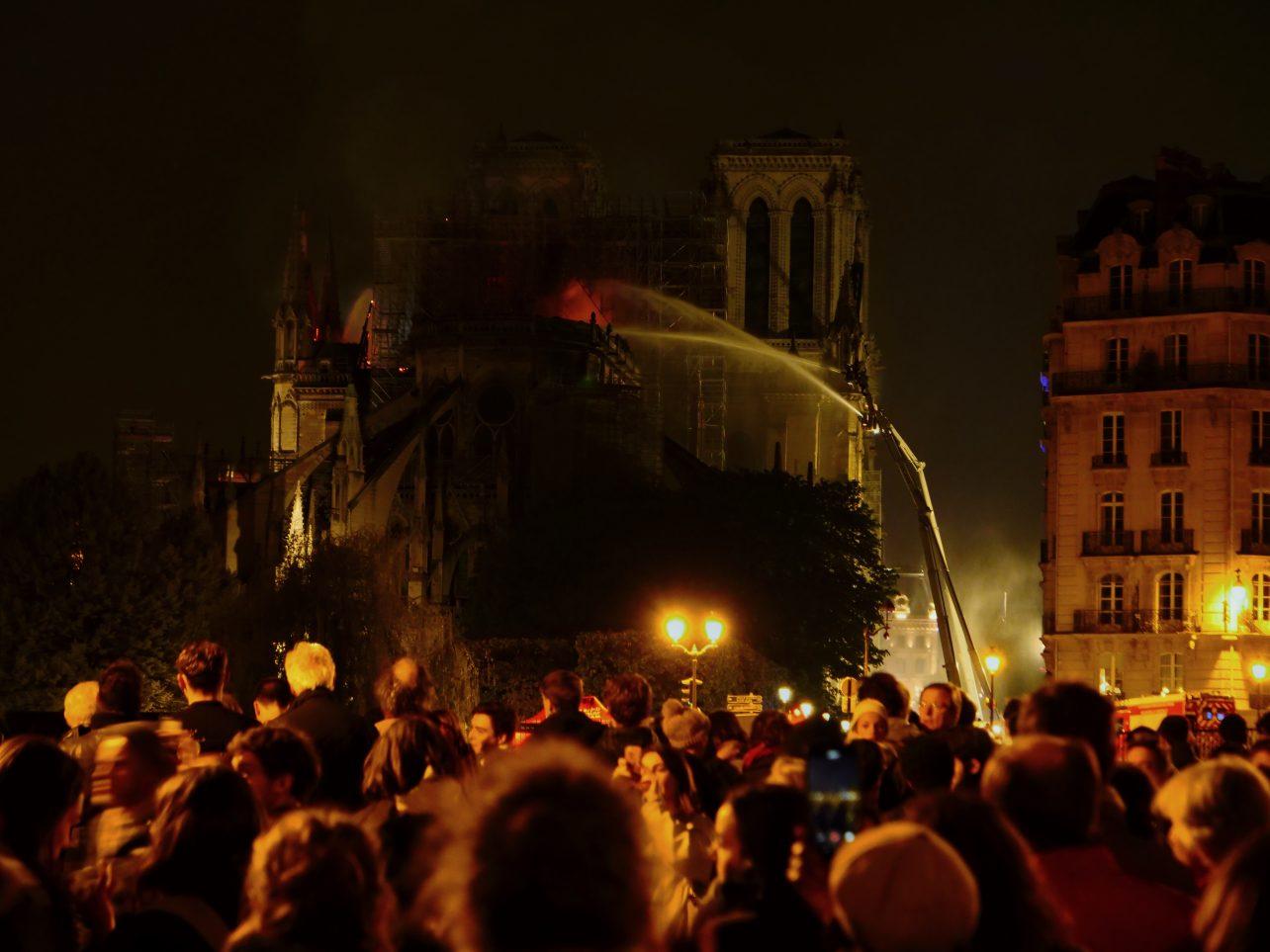Une foule de parisiens regardant Notre Dame brûler dans la nuit du 15 au 16 avril