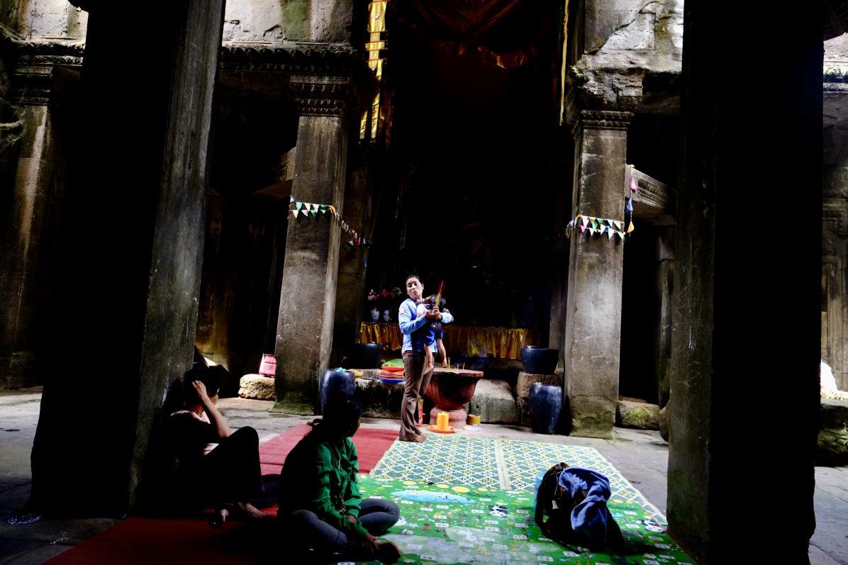 Une garde des temples d'Angkor et quelques locaux priant à un petit temple improvisé