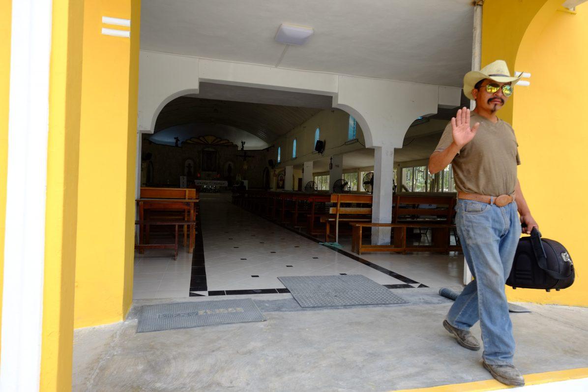 Un mexicain sortant d'une petite église colorée de Tulum